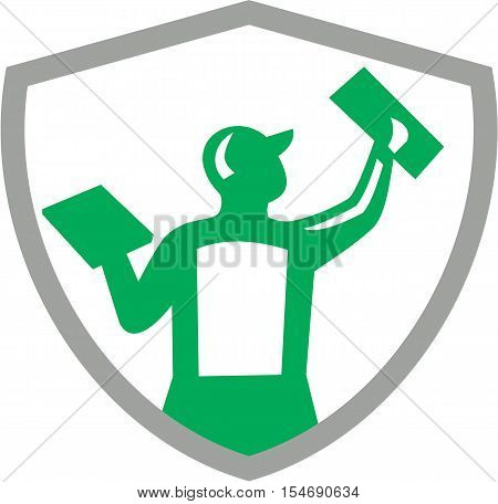 Illustration of a plasterer masonry tradesman construction worker holding trowel plastering viewed from rear set inside shield crest on isolated background done in retro style.