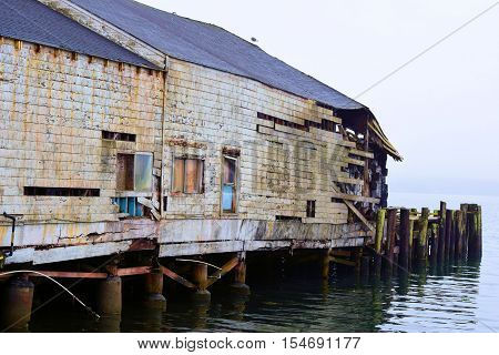 dilapidated warehouse building which once stored seafood taken on a rustic pier in Bodega Bay, CA