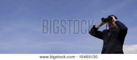 Businessman looking through binoculars with a blue sky as background (very wide photo)