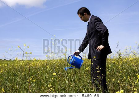 businessman at the field with a flowerpot in his hand