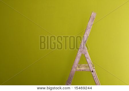 a construction ladder on a green wall