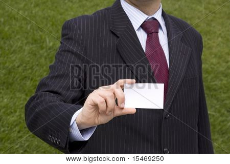 Businessman showing a blank card with copy space (selective and soft focus)