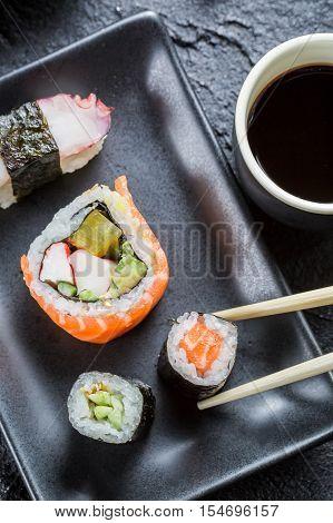 Sushi on black ceramic eaten with chopsticks