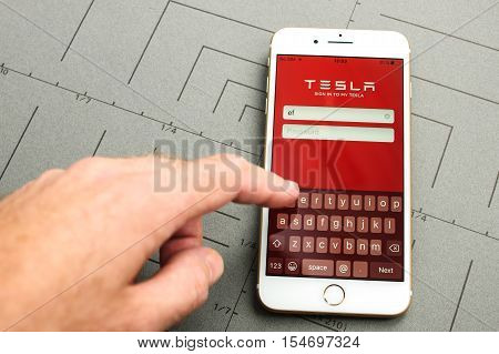 PARIS FRANCE - SEPT 26 2016: New iPhone 7 Plus with hand touching screen to sign-in to Tesla Electric car module app. iPhone 7 and iPhone 7 plus is the most wanted phone worldwide