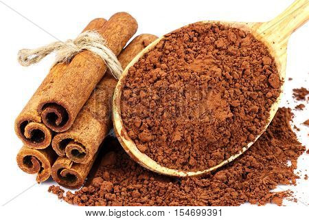 Group of cinnamon sticks and cacao powder in wooden spoon isolated on white background close-up
