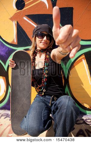 cool skateboard woman next to a graffiti wall. The Graffiti is illegal art in a public park.