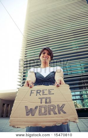 unemployed woman showing a message in a cardboard that she is free to work (cross processed image)