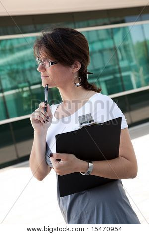 modern businesswoman writing on her notebook next to her office