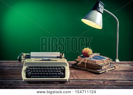 Lamp and typewriter in the classroom on old wooden table