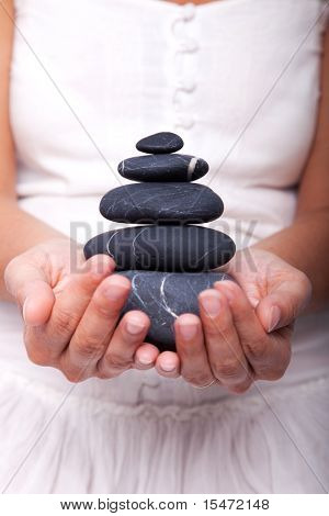 hands holding a stack of black stones (selective focus)