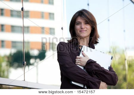 businesswoman with her laptop next to the office