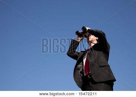 Businessman looking through binoculars with a blue sky as background