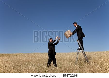 businessman in a step ladder passing a box to the one on the field