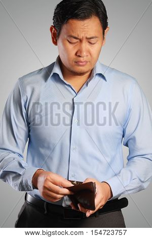 Photo image portrait of a young Asian businessman with empty wallet no money in purse for saving businessman looking empty purse sad businessman and bankruptcy concept