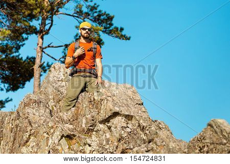 A young male with a beard is traveling through the mountain, a tourist with a rucksack standing on the rock hill while enjoying nature view, summer holidays in the mountains.