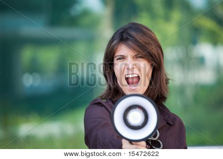 businesswoman shouting at the megaphone next to her office