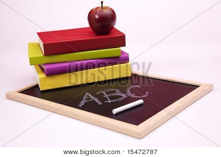 ABC letters written on a blackboard with colorful books (selective focus)
