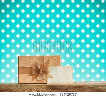 holiday brown gift box with a bow paper label on a wooden table turquoise background with polka dots