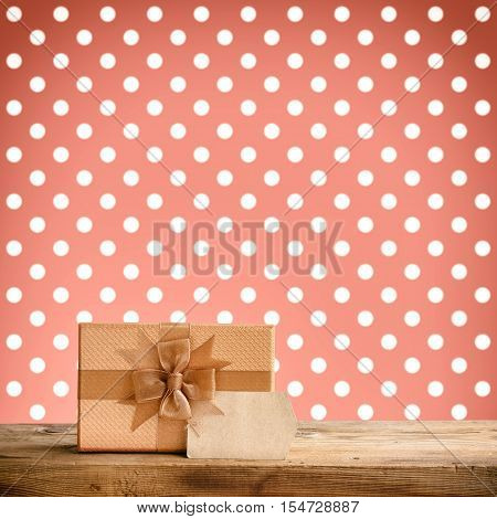 festive brown gift box with bow paper label on wooden table background with polka dots retro styled