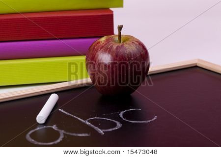 Back to school letters written on a blackboard with colorful books (selective focus)