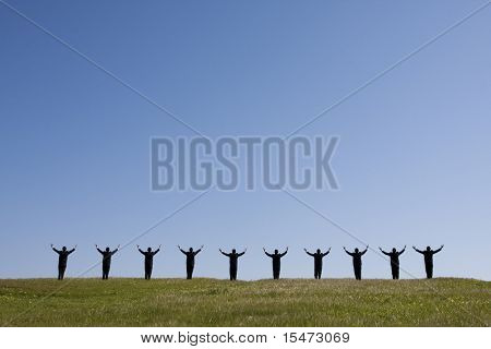 large group of businessman in the field with his arms outstretched