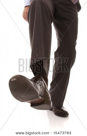 shoe and leg of a businessman caution step (selective focus)