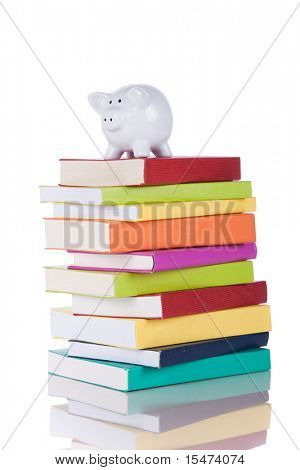piggy bank over a stack of colorful books (isolated on white)