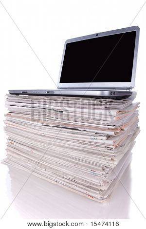Laptop over a stack of newspapers for internet information access (isolated on white)