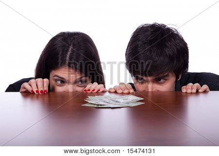 Men and woman looking to a lot of money over the table