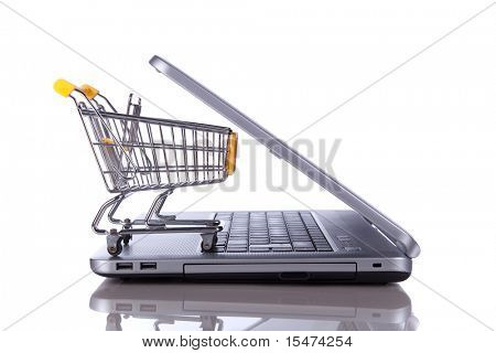 shopping cart over a laptop isolated on white with reflection