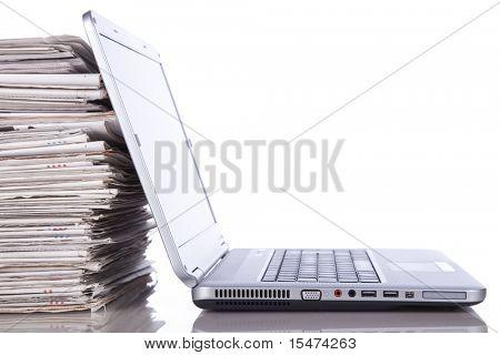 pila del periódico junto a una computadora portátil (aislada en blanco)