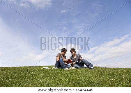 dos libros de lectura de joven estudiante en el Parque de la escuela