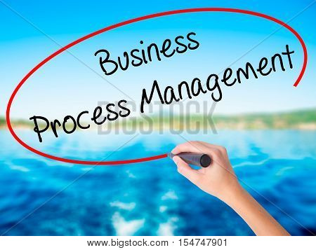Woman Hand Writing Business Process Management With A Marker Over Transparent Board
