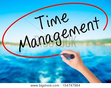 Woman Hand Writing Time Management With A Marker Over Transparent Board