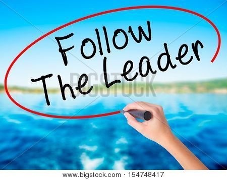 Woman Hand Writing Follow The Leader With A Marker Over Transparent Board