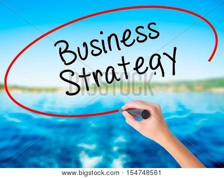Woman Hand Writing Business Strategy With A Marker Over Transparent Board
