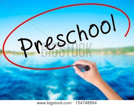 Woman Hand Writing Preschool With A Marker Over Transparent Board