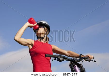 Biker woman refreshing drinking water at her morning exercise