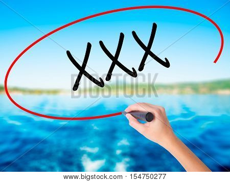 Woman Hand Writing Xxx With A Marker Over Transparent Board