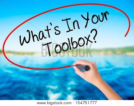 Woman Hand Writing  What's In Your Toolbox? With A Marker Over Transparent Board