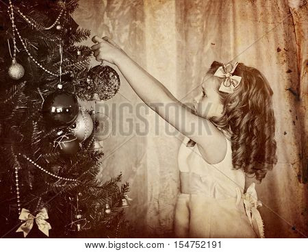 Retro old portrait of child girl decorate on Christmas tree. Black and white retro picture.