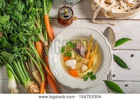 Homemade broth with noodles on old table