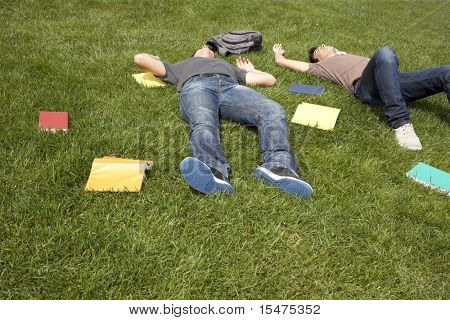 two young student lying down at the school grass after long hours of study