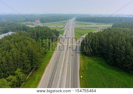 Tyumen, Russia - July 22, 2016: Bird eye view onto two-level outcome of roads on Irbit path with bypass way. There is smog in air