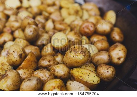 Country fair cooking. Roasted potatoes cooked by vendor outdoors in big metal cauldron pot. Cookout meals bbq closeup. Fresh organic, healthy snack, potatoes on grill. Street food, fast food.