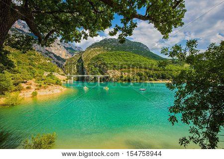 National park Merkantur, Provence, France. Large bridge over the gorge and  river Verdon. White catamarans are sailing on turquoise water