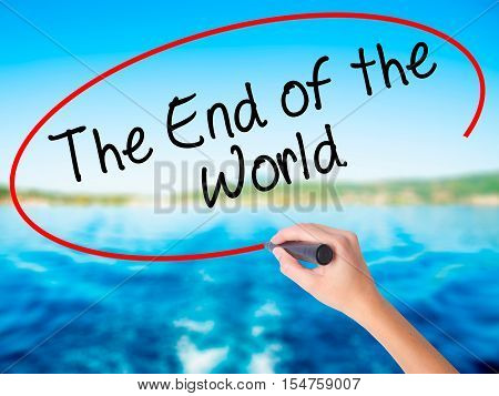 Woman Hand Writing The End Of The World With A Marker Over Transparent Board