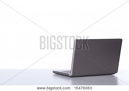 Laptop at the desk in the office isolated on white