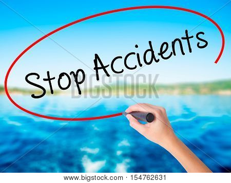 Woman Hand Writing Stop Accidents With A Marker Over Transparent Board