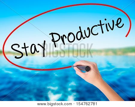 Woman Hand Writing Stay Productive With A Marker Over Transparent Board